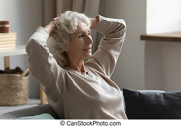 Hoary woman relaxing on couch with folded hands behind head.