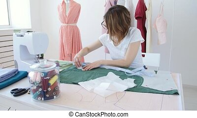 Hobby and small business. Young pretty female tailor working with cloth fabric in workshop