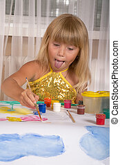 Little girl draws a summer landscape on the big sheet of a paper.