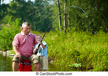 Photo of grandfather and grandson fishing on weekend