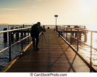 Hobby photograph with camera on tripod in hand. Wooden board  bridge