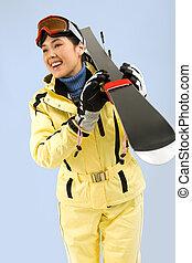 Portrait of pretty woman in sportswear carrying her skis