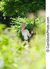 Hobbyist gardener in the garden - Smiling hobbyist senior ...