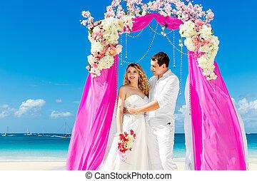 hochzeitsfeier, auf, a, tropischer strand, in, purple., glücklich, stallknecht, und, braut, unter, der, bogen, dekoriert, mit, blumen, auf, der, tropische , sand, strand., wedding, und, flitterwochen, concept.