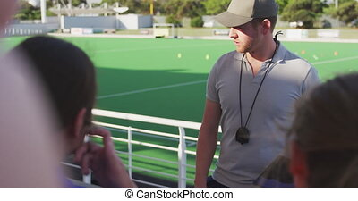 Front view of a Caucasian male coach standing and instructing a teenage Caucasian female hockey team, sitting on stadium seats at a sports field, slow motion