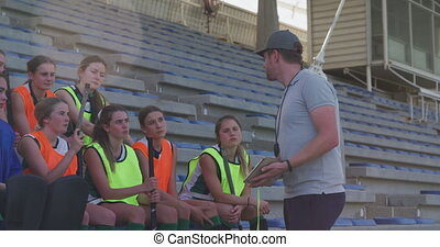 Side view of a Caucasian male coach standing and instructing a teenage Caucasian female hockey team, sitting on stadium seats at a sports field, lens flare, slow motion