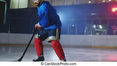 Hockey forward carrying a puck, skating past an opposing...