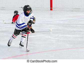 A young hockey player races with the puck.