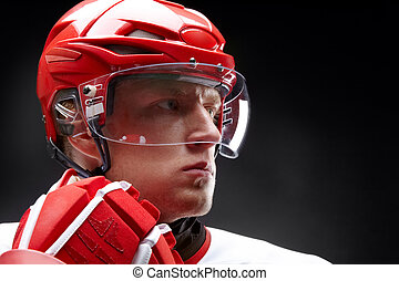 Hockey-player - Portrait of a hockey player against black...