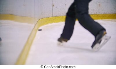 Hockey player throws the puck into enclosure wall. Slow motion