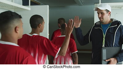 Front view of a multi-ethnic group of teenage field hockey players preparing before a game, standing in a row in a changing room, walking forwards, high fiving their Caucasian male coach, in slow motion