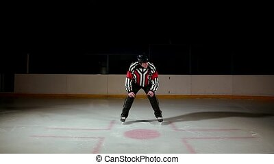 hockey referee produces a faceoff and the two players begin ...