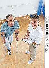 hoge hoek, verticaal, van, een, mannelijke , therapist, het bespreken, rapporten, met, een, invalide, patiënt, in de gymnastiek, op, ziekenhuis