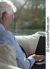 hogere mens, gebruikende laptop
