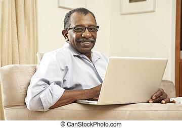 hogere mens, gebruikende laptop, thuis