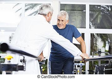 hogere mens, kijken naar, arts, terwijl het lopen, in, fitness, studio