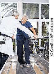 hogere mens, kijken naar, arts, terwijl het lopen, in, rehab, centrum