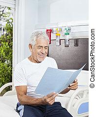 hogere mens, kijken naar, rapporten, op bed, in, rehab, centrum