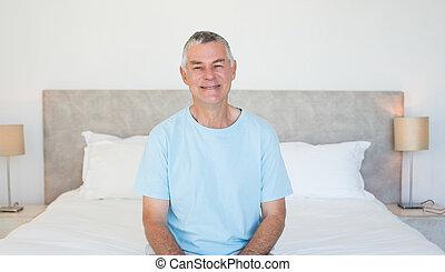 hogere mens, zitting op het bed