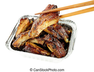 Hoisin sauce Chinese pork ribs in a foil take away tray isolated on a white background