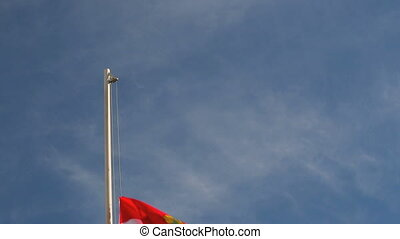 Hoist a Hungary flag in front of blue sky
