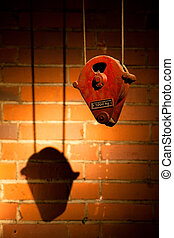 Hoist for lifting heavy weight old industrial winch to lift cargo, with shadow on red wall.