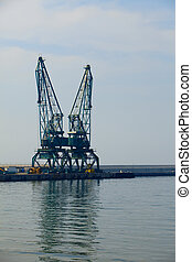 Hoisting crane and reflection of it at sea In port