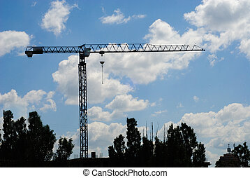 hoisting crane over the blue sky with clouds