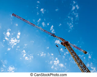 Working hoisting crane against blue sky with clouds.
