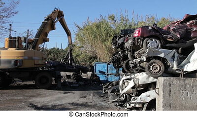 Hoisting smashed cars - Gripper moving smashed cars who are...
