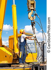 Hoisting works - Construction worker in uniform and...