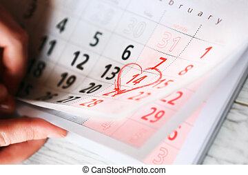 hoja, de, calendario de pared, con, corazón rojo, marca, en, 14, febrero, -, día de valentines