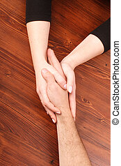 Woman's hands holding man's hand