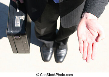Business man in black suit, holding briefcase, is standing with one hand open waiting for his payment