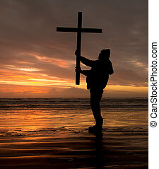 Man holding a cross at sundown