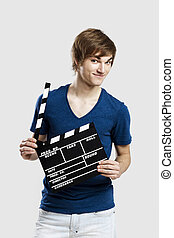Holding a clapboard - Casual young man holding a clapboard,...