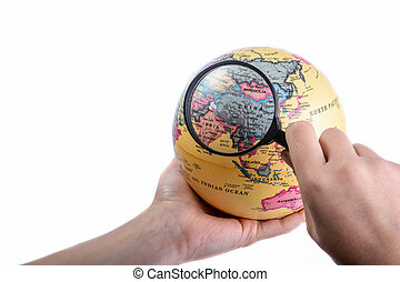 Holding a magnifying glass on globe