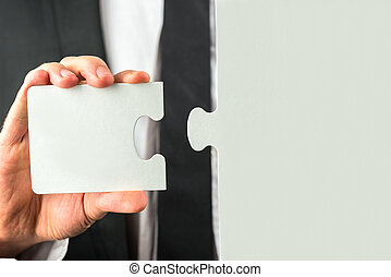 Holding a missing piece of a puzzle - Businessman holding...