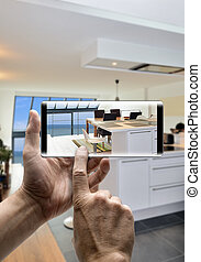 Two hands holding a mobile Smartphone and take a picture of a american kitchen