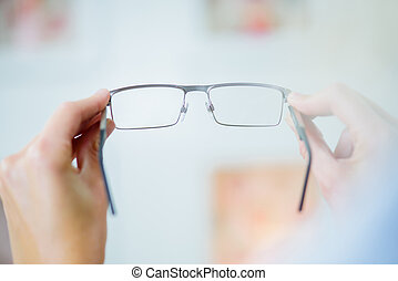 holding a pair of glasses