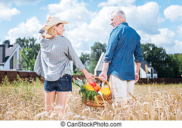 Loving husband and wife holding nice big basket with their vegetables together
