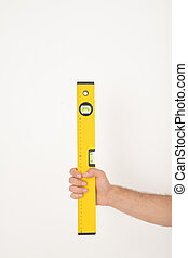 Close-up of unrecognizable repairman holding yellow construction level against isolated background