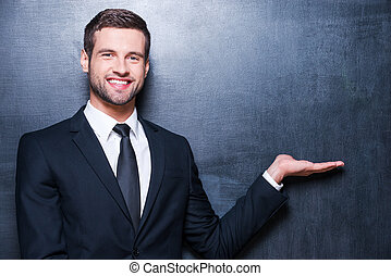 Holding copy space. Handsome young man in formalwear looking at camera and holding copy space while standing against blackboard
