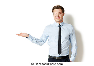 Holding copy space. Handsome young man in shirt and tie ...