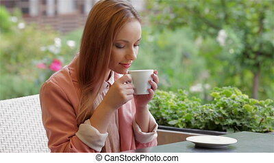 Holding cup and inhaling the aroma - Cheerful woman is...