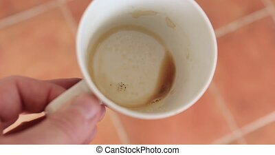 Holding empty coffee cup in sunlight on the balcony, coffee ran out