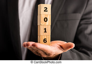 Holding four stacked wooden cubes with 2016 sign