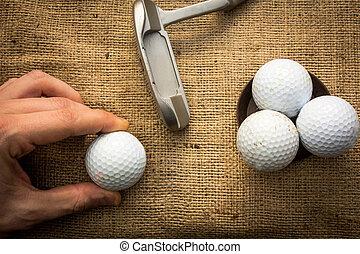 A hand holding a golf ball near a putter and three other golf balls