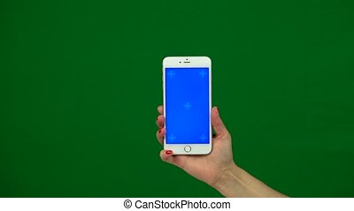 Holding hand a mobile smartphone blue screen. Green screen -...