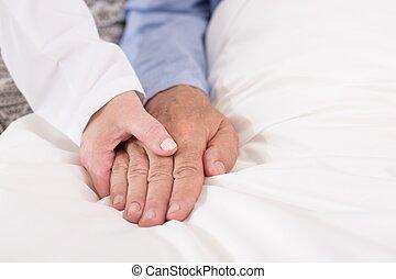 Holding hand of sick man
